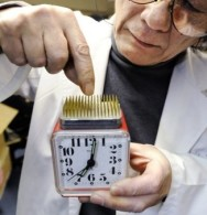 "Kenji Kawakami, inventor and founder of the International Chindogu Society demonstrates an alarm clock with the ""snooze"" button located in the middle of a bed of sharp pins designed to help keep user awake in Tokyo on June 3, 2009. The word ""Chindogu"" translates as ""weird tools"" and Kawakami has invented hundreds of these often bizzare and absurd items. AFP PHOTO/YOSHIKAZU TSUNO (Photo credit should read YOSHIKAZU TSUNO/AFP/Getty Images)"